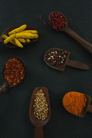Various spices in wooden scoop