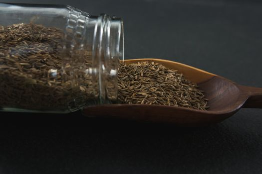 Cumin spilling out of jar into scoop