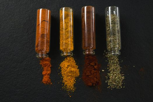 Various spices spilling out of bottles
