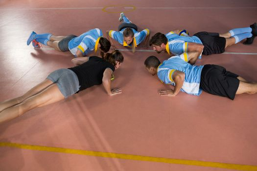 Volleyball team doing push-ups with coach