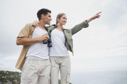 Hiking couple with binoculars on mountain terrain