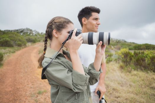 Couple taking picture on mountain terrain