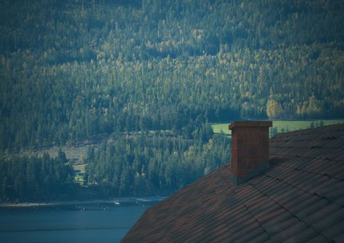 Roof with chimney and forest mountain