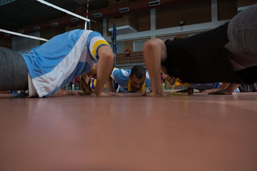 Coach doing push-ups with volleyball players