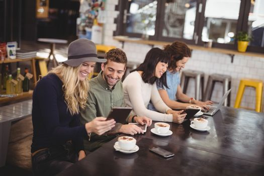 High angle view of happy friends using technologies while sitting at table in coffee shop
