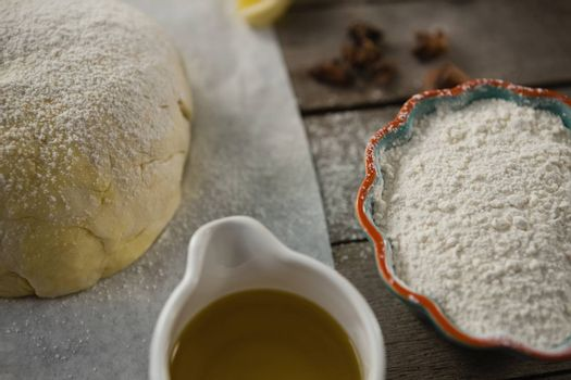 High angle view of dough and flour with cooking oil on table