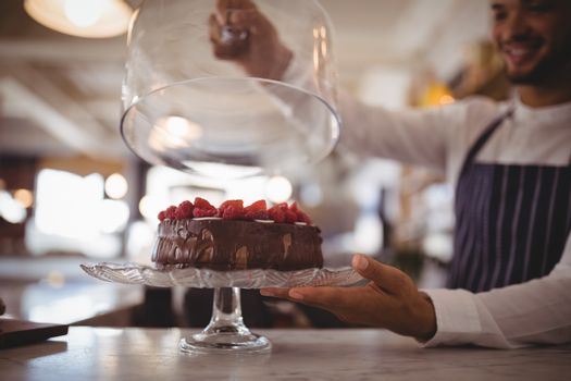 Close up of young waiter holding glass lid over cake on cakestand at counter