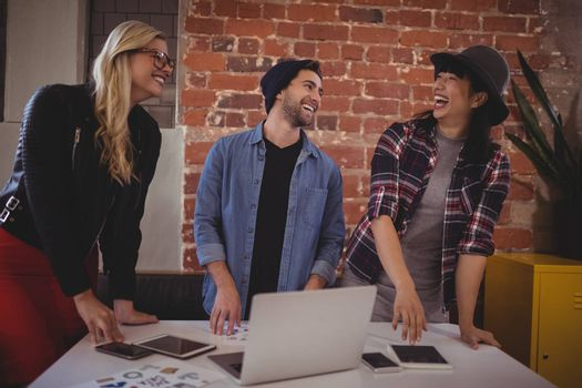 Cheerful young creative team using technologies while standing by table at coffee shop