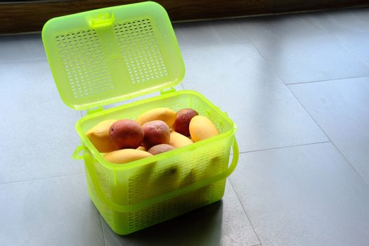 Light-green plastic basket or container with fresh exotic fruits yellow mango and passion. Top view close up.