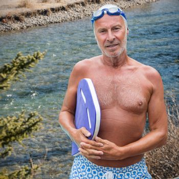 Composite image of portrait of senior male swimmer with swimming float