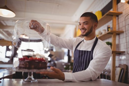Smiling young waiter holding glass lid over cakestand at counter