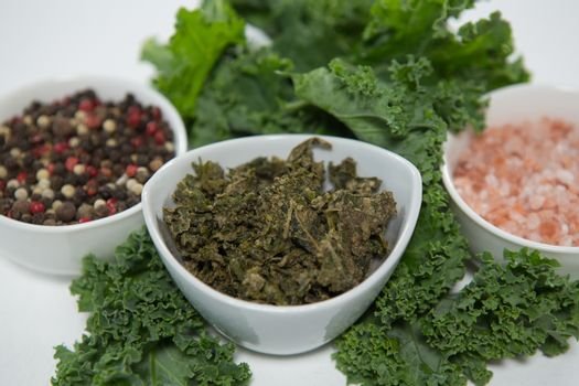 Close up of peppercorn and salt with kale
