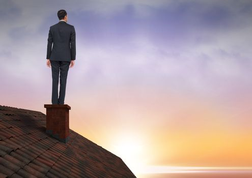 Businessman on roof chimney with sunset