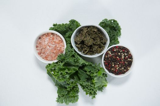 Overhead view of salt and peppercorn with kale
