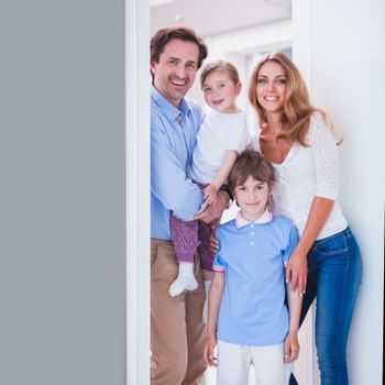 Cheerful family of parents and two children inviting to enter in home standing in doorway