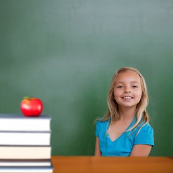 Red apple on pile of books against cute pupil smiling