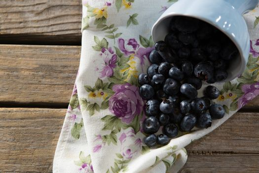 Blueberries spilling out of bowl on napkin