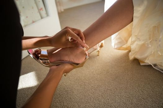 Cropped hands of beautician putting on sandal to bride at home