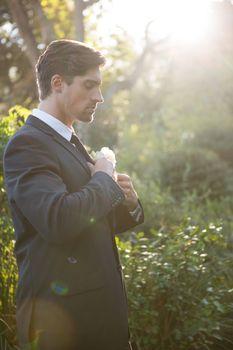 Confident bridegroom adjusting necktie in park