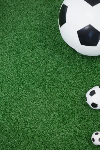 Various size of footballs on artificial grass