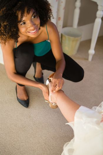 High angle view of smiling beautician putting on sandal to bride