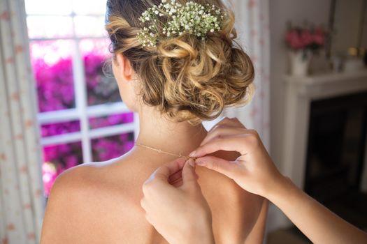 Bridesmaid fastening bride chain in dressing room