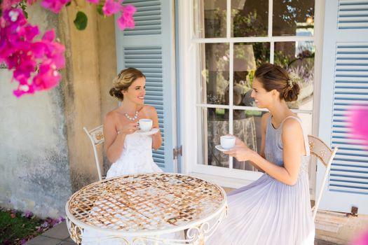 Bride and bridesmaid having coffee in yard