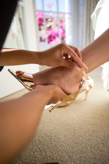 Cropped hands of beautician putting on sandal to bride