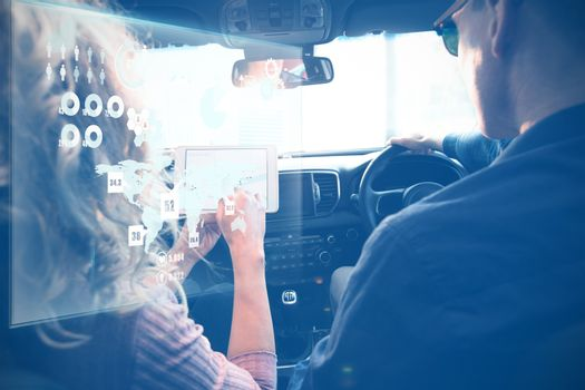 Global technology background against couple looking at tablet on a car