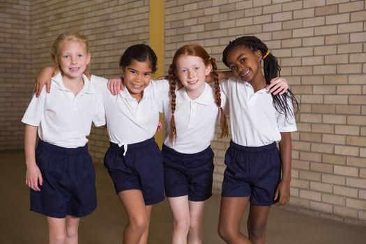 Cute pupils smiling at camera in PE uniform