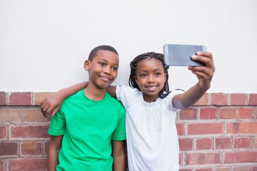 Cute pupils taking a selfie in the corridor at the elementary school