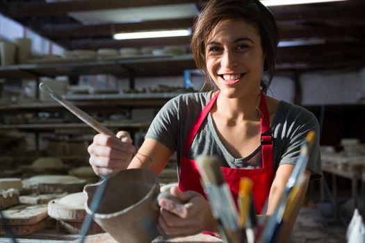 Portrait of female potter carving mug