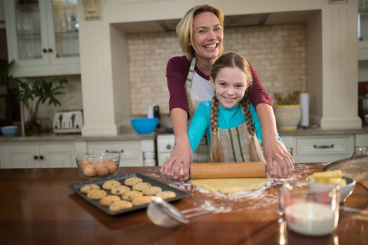 Mother and daughter rolling dough with rolling pin in kitchen
