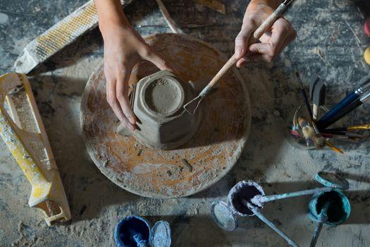 Hands of female potter carving mug