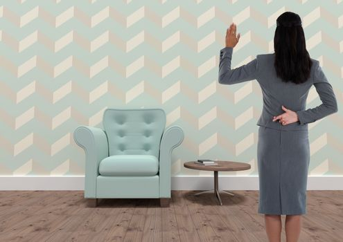 Businesswoman with fingers crossed in quirky wallpapered room with armchair