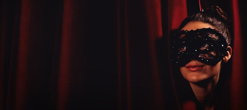 Artist in mask peeking through curtain