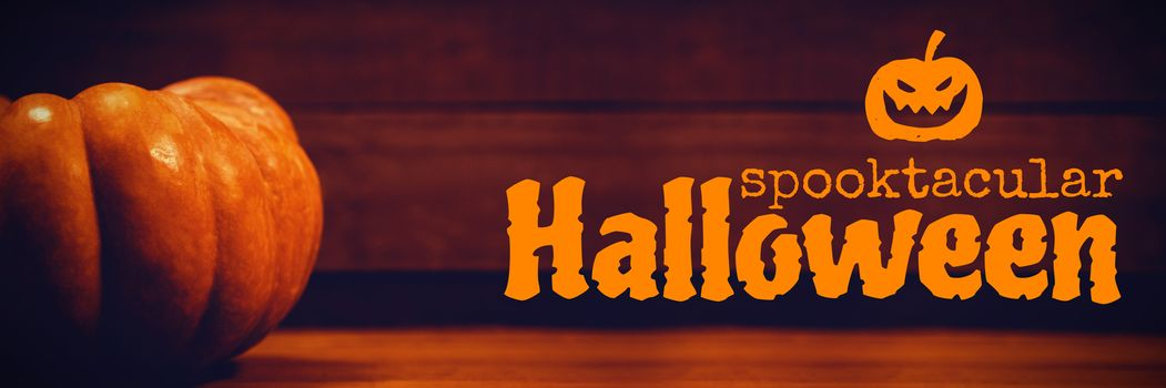 Graphic image of spooktacular Halloween text against pumpkin on table during halloween