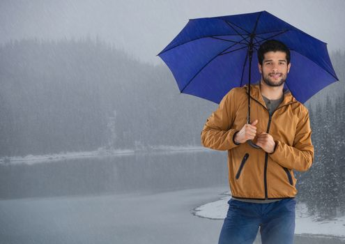 Man with umbrella over icy lake