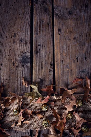 Sequin balls and dry leaves on wooden plank