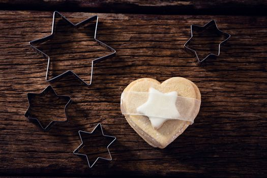 Cookie cutter and cookie on wooden plank