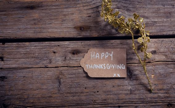 Thanksgiving card and flora on wooden plank
