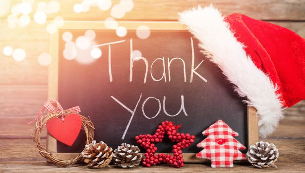 Thank you text on slate with decorations on wooden table during Christmas time