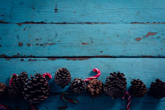 Pine cone and candy cane arranged on wooden plank