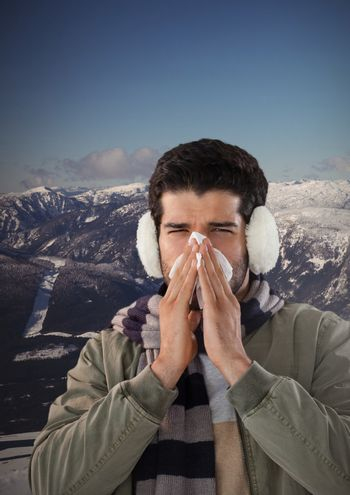 Man blowing nose with earmuffs and snow mountain landscape