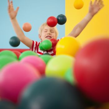 Happy boy playing in ball pool