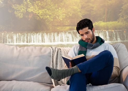 Man in Autumn reading a book by waterfall foggy imagination