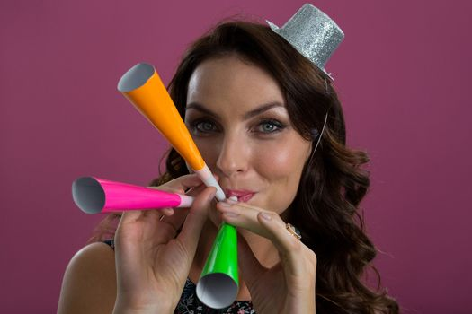 Woman in sliver hat blowing party horns