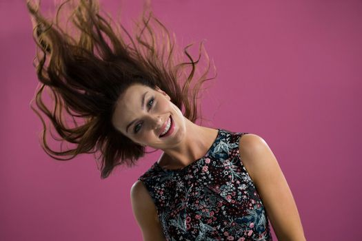 Smiling woman tossing her long hair