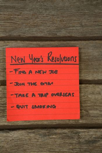 New year resolution written on sticky notes on wooden surface