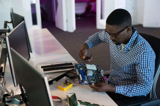 Computer engineer repairing motherboard at desk